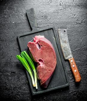 Raw liver on a cutting board with green onions. on black rustic background