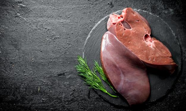 石の板にディルが付いた生の肝臓。黒の素朴な背景に