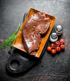まな板にハーブ、トマト、スパイスを添えた生の肝臓。暗い素朴な表面に