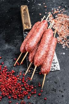 Сырой люля или кебаб с солью и перцем насаживают на нож для мясника. черный фон. вид сверху.
