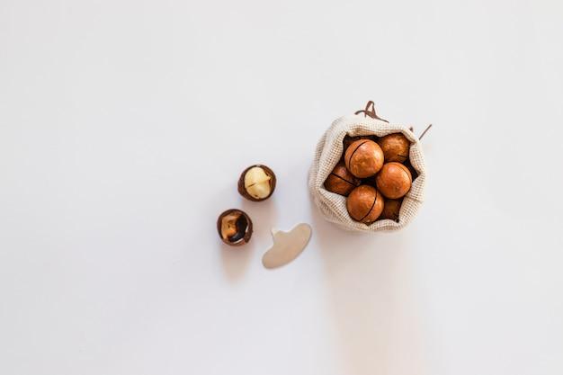 흰색 단색 배경에 캔버스 그릇에 생 마카다미아 너트. 최소한의 평면 구성