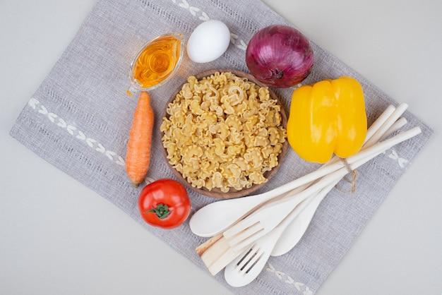 Сырые макароны с овощами на деревянной тарелке на скатерти
