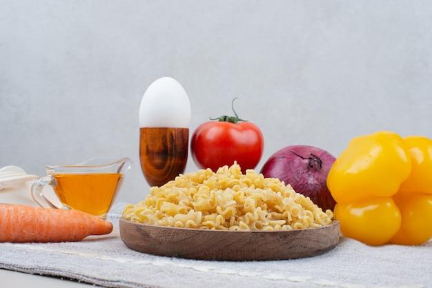 식탁보에 나무 접시에 야채와 원시 마카로니