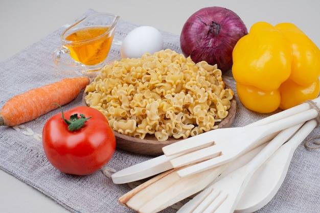 Maccheroni crudi con le verdure sul piatto di legno sulla tovaglia