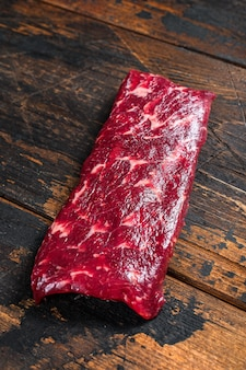 Raw machete or skirt beef steak. dark wooden table. top view.
