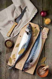 Raw mackerel fish with ingredients for cooking on a wooden old surface