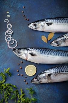 青いコンクリートまたは石の背景で調理するための材料と生のサバの魚。