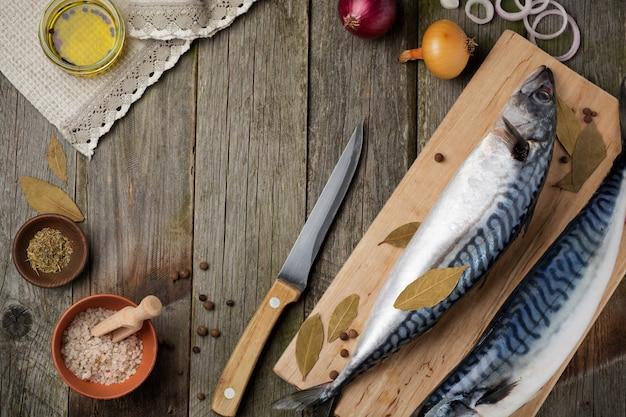 木製の古い背景の素朴なスタイルで調理するための材料と生のサバの魚。 。