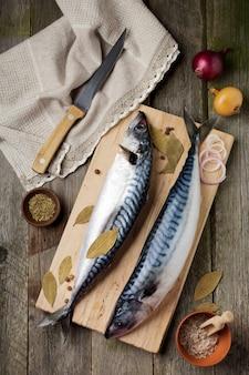 木製の古い表面で調理するための材料と生のサバの魚