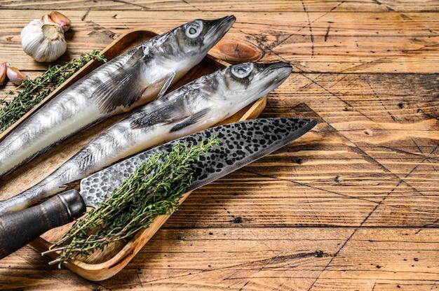 Сырая ледяная рыба скумбрии в деревянном подносе. деревянный фон. вид сверху. скопируйте пространство.