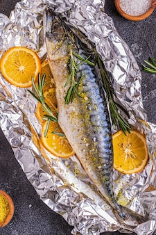 Raw mackerel with spices in baking foil, top view
