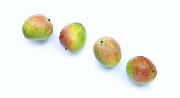 Raw mango on white background. top view