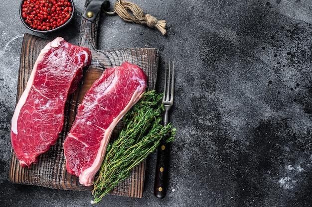 生の霜降り牛肉のサーロインステーキ。黒の背景。上面図。スペースをコピーします。