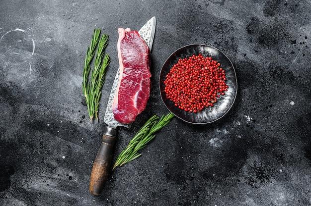 Raw marbled beef meat strip loin steak on a knife