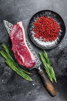 生の霜降り肉のサーロインステーキをナイフで。上面図。