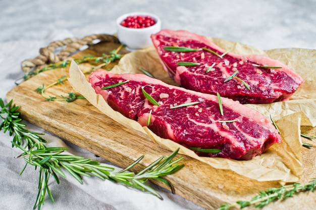 Raw marbled beef steak black angus on a wooden chopping board with rosemary and pink pepper.
