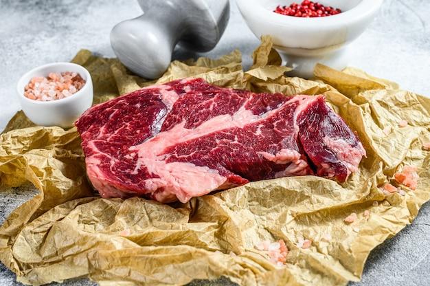 Сырой мраморный стейк из говядины на разделочную доску. органическая ферма мяса черного ангуса. серый фон