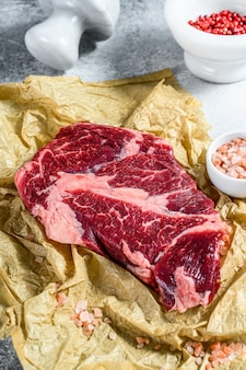 Сырой мраморный стейк из говядины на разделочную доску. органическая ферма мяса черного ангуса. серая стена