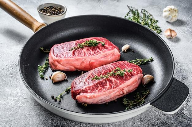 Сырой стейк из мраморной говядины, мясной стейк по верхнему лезвию. серый фон. вид сверху.