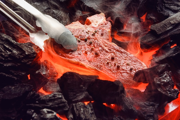 Raw marbled beef steak with coals and smoke