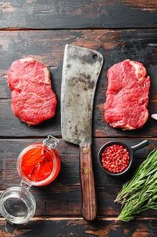 Стейк из сырой мраморной говядины со старым ножом для мясника и приправами