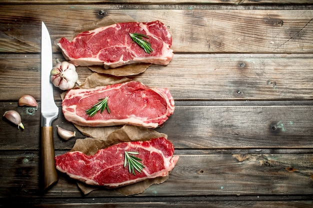 Raw marbled beef steak with spices on rustic table.