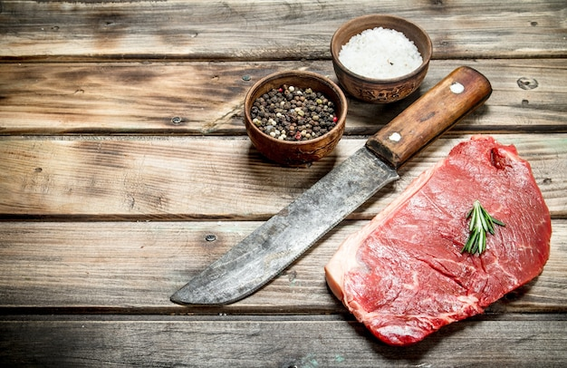 Raw marbled beef steak with spices on wooden table.