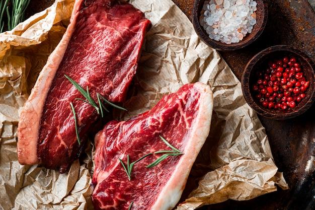 古い木製の背景の上面図での準備のための生の霜降りビーフステーキと調味料