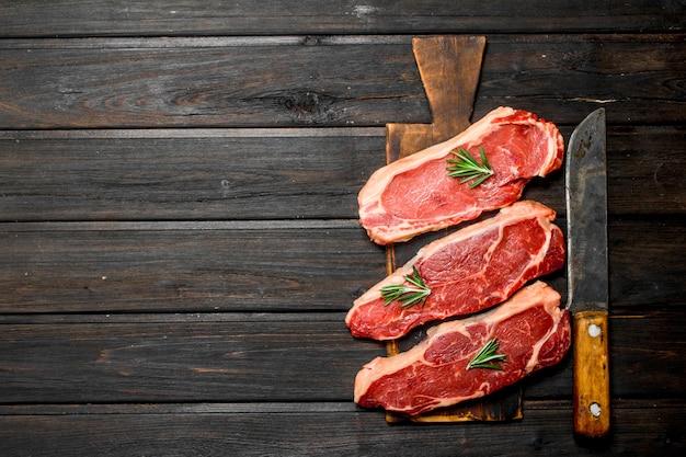 나무 테이블에 원시 차 돌 박이 쇠고기 스테이크.