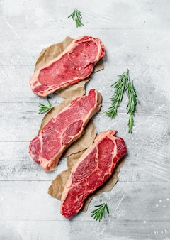 Raw marbled beef steaks with fragrant rosemary. on a rustic background.