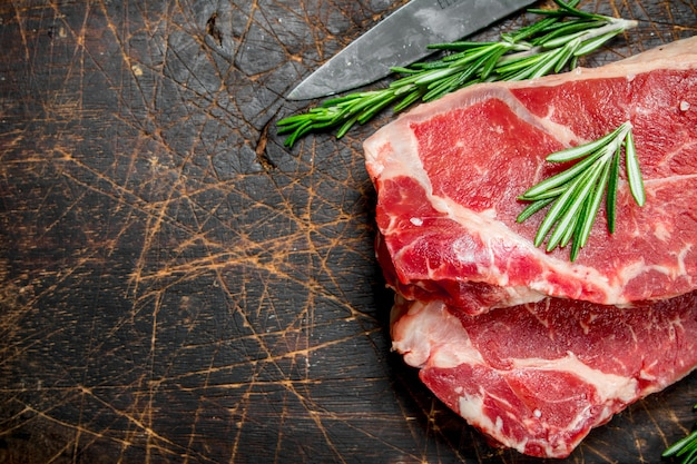 Raw marbled beef steaks with rosemary. on a wooden background.
