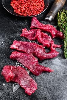 Сырое мраморное мясо нарезать тонкими полосками для бефстроганова. вид сверху.