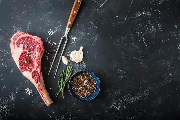 生の霜降り肉ステーキ、フォーク、調味料、素朴な石の背景。テキスト用のスペース。骨付きビーフリブアイステーキ、調理の準備ができています。