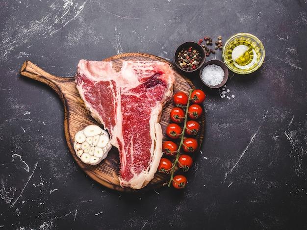 Raw marbled meat steak t-bone, seasonings, vegetables, rustic stone background.