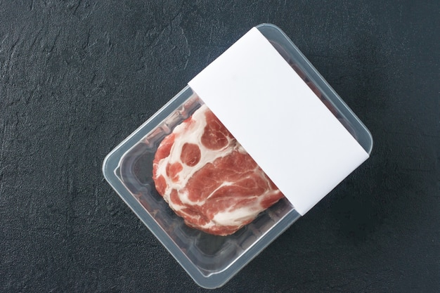 Raw marbled pork steak in vacuum packaging on black background, top view, logo mockup for design.