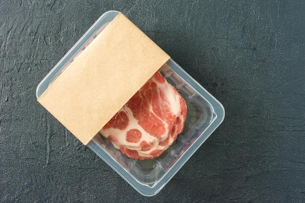 Raw marbled pork steak in vacuum packaging on black background, top view, logo mockup for design