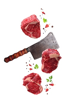 Raw marbled ribeye steak and butchers knife isolated