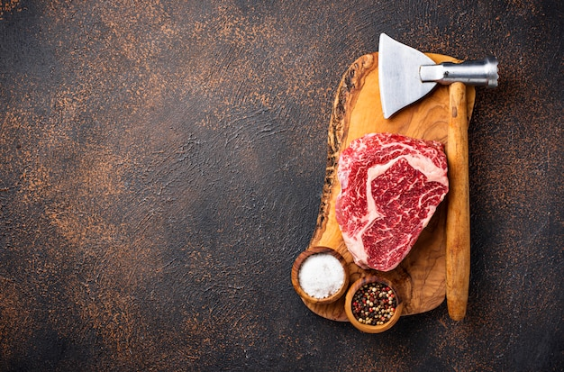 Raw marbled ribeye steak and butchers knife
