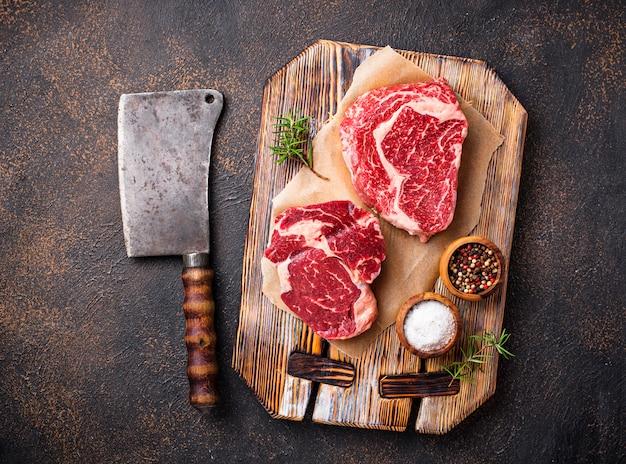 Raw marbled ribeye steak and butchers knife