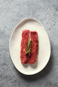 Raw marbled ribeye steak with rosemary on grey. top view. vertical format.