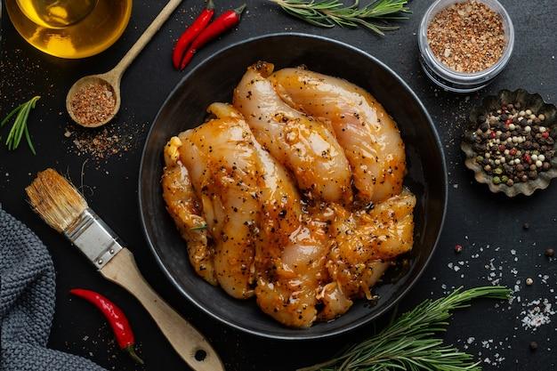 暗い表面に生のマリネした鶏の胸肉とスパイスを調理する準備ができている
