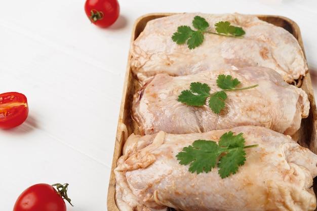 木の板に生のマリネした鶏の胸肉をクローズアップ
