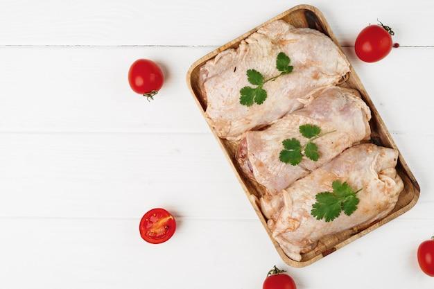 木の板に生のマリネした鶏の胸肉