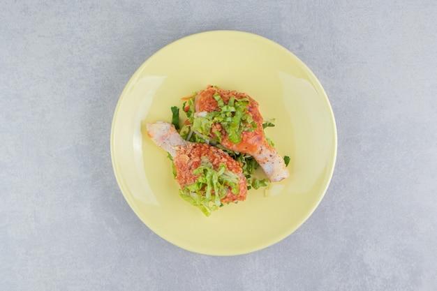 Сырое маринованное куриное мясо, куриные окорочка в тарелке, на белой поверхности