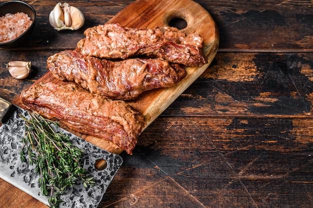 Сырые маринованные стейки юбки в соусе барбекю на деревянной разделочной доске с травами на деревянном столе. вид сверху.