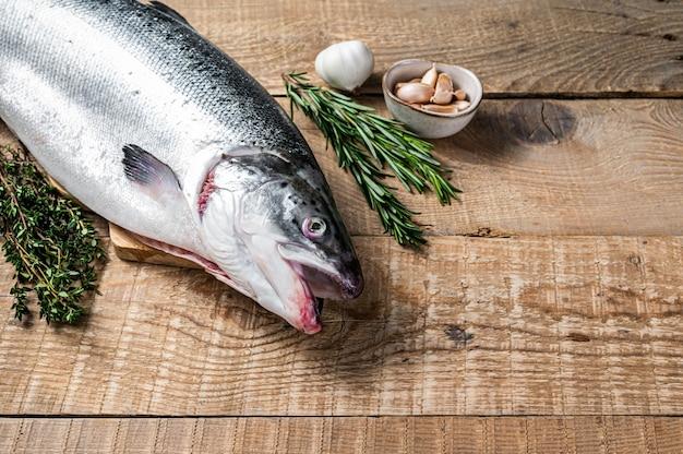 Сырая морская рыба лосося на деревянном столе кухни с травами. деревянный фон. вид сверху. скопируйте пространство.