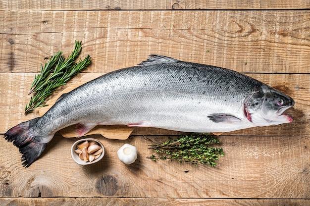 ハーブと木製のキッチンテーブルで生の海のサーモンの魚。木製の背景。上面図。