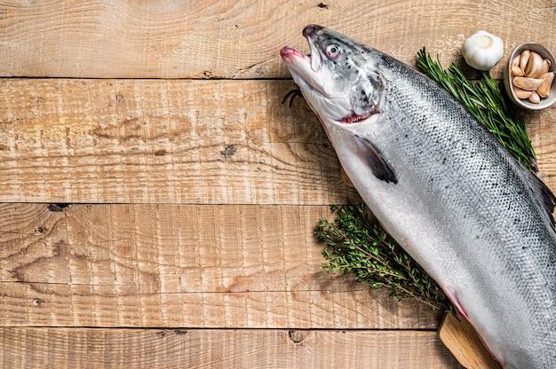 ハーブと木製のキッチンテーブルの上の生の海のサーモンの魚