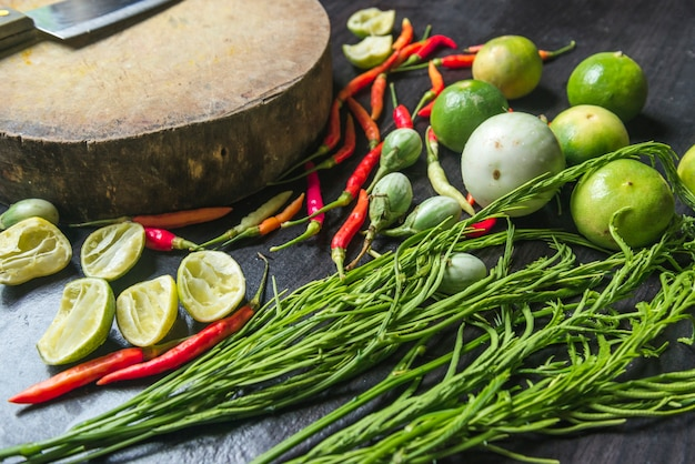 Сырые сырьевые овощи разрушаются, готовятся к приготовлению на черном деревянном фоне