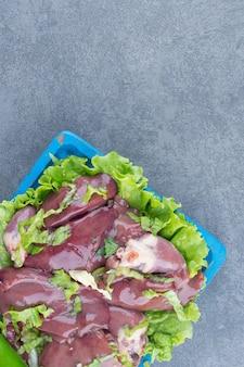 Сырое мясо и куриная ножка на синей доске.